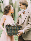 Les beaux nouveaux mariés de sourire brouillés tiennent la boîte tissée avec les furets gris dans la forêt Photos stock