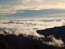 Les beaux nuages dans le ciel forment le dessus de la montagne image stock