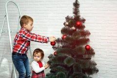 Les beaux petits enfants décorent l'arbre de Noël Joyeux Noël Photo libre de droits