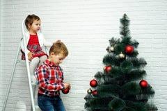 Les beaux petits enfants décorent l'arbre de Noël Joyeux Noël Photos stock