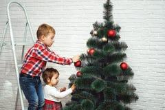 Les beaux petits enfants décorent l'arbre de Noël Joyeux Noël Images libres de droits