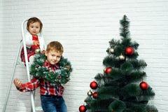 Les beaux petits enfants décorent l'arbre de Noël Joyeux Noël Image libre de droits