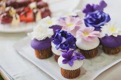 Les beaux petits gâteaux faits maison avec le massepain pourpre, blanc et rose fleurit sur le dessus photos libres de droits