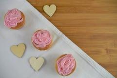 Les beaux petits gâteaux roses avec le coeur d'amour forme pendant un jour de mères Images stock
