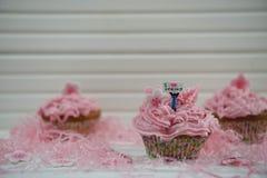 Les beaux petits gâteaux roses décorés d'une figurine miniature de personne tenant un signe indiquant l'amour d'I jaillissent Image stock
