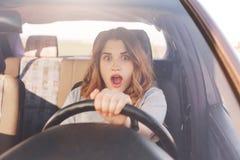 Les beaux realzes femelles européens choqués de conducteur qui sa voiture est brocken, peuvent réparation du ` t il seule, voit l Image libre de droits