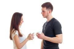 Les beaux supports de brune vis-à-vis d'un jeune gentil type et eux tiennent ensemble des tasses de thé dans les mains Photos stock