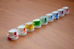 Les becs multicolores salis du pulvérisateur de peinture sont alignés sur une table en bois Concep d'art de rue Image libre de droits