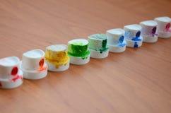 Les becs multicolores salis du pulvérisateur de peinture sont alignés sur une table en bois Concep d'art de rue Photographie stock