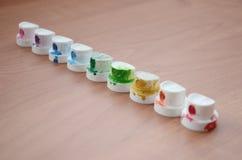 Les becs multicolores salis du pulvérisateur de peinture sont alignés sur une table en bois Concept d'art de rue photos stock
