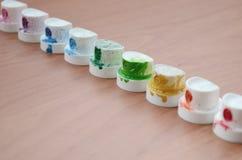 Les becs multicolores salis du pulvérisateur de peinture sont alignés sur une table en bois Concept d'art de rue images libres de droits