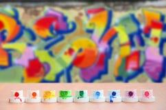 Les becs multicolores salis du pulvérisateur de peinture sont alignés sur une table en bois sur un fond du dessin coloré de graff Photographie stock libre de droits