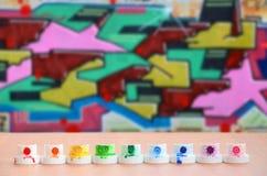 Les becs multicolores salis du pulvérisateur de peinture sont alignés sur une table en bois sur un fond du dessin coloré de graff Photos libres de droits