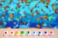 Les becs multicolores salis du pulvérisateur de peinture sont alignés sur une table en bois sur un fond du dessin coloré de graff Image libre de droits