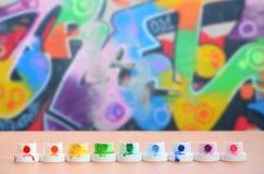 Les becs multicolores salis du pulvérisateur de peinture sont alignés sur une table en bois sur un fond du dessin coloré de graff Photo libre de droits