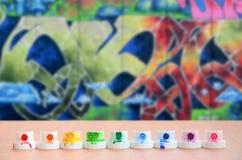 Les becs multicolores salis du pulvérisateur de peinture sont alignés sur une table en bois sur un fond du dessin coloré de graff Images stock