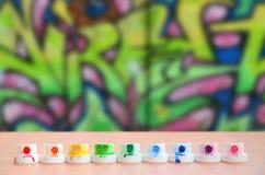 Les becs multicolores salis du pulvérisateur de peinture sont alignés sur une table en bois sur un fond du dessin coloré de graff Images libres de droits
