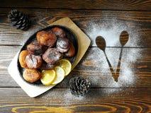 les beignets faits maison ont fait frire dans une casserole de fonte, arrosée avec du sucre en poudre avec des cônes sur un en bo Images stock