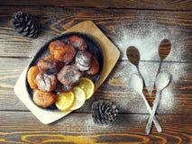 les beignets faits maison ont fait frire dans une casserole de fonte, arrosée avec du sucre en poudre avec des cônes sur un en bo Photos libres de droits
