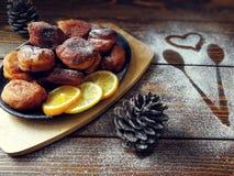 les beignets faits maison ont fait frire dans une casserole de fonte, arrosée avec du sucre en poudre avec des cônes sur un en bo Images libres de droits