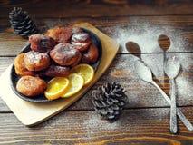 les beignets faits maison ont fait frire dans une casserole de fonte, arrosée avec du sucre en poudre avec des cônes sur un en bo Photo libre de droits