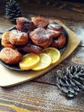 les beignets faits maison ont fait frire dans une casserole de fonte, arrosée avec du sucre en poudre avec des cônes sur un en bo Photographie stock libre de droits