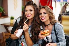 Les belles amies avec composent la consommation en café d'aliments de préparation rapide Photos libres de droits
