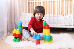 Les belles 2 années d'enfant en bas âge joue les blocs en plastique Images libres de droits