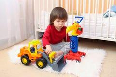 Les belles 2 années de garçon d'enfant en bas âge joue des voitures à la maison Photos stock