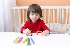 Les belles 2 années de garçon dans la chemise rouge joue avec le playdough Image libre de droits