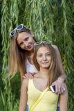 Les belles deux soeurs, amies se garent, souriant, la nuance heureuse et détendante des arbres, parc d'été dans des lunettes de s Images libres de droits