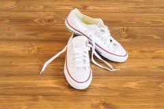 Les belles espadrilles blanches se tiennent sur le plancher en bois foncé Photographie stock