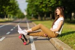 Les belles espadrilles T-shirt et pantalon de hippie de jeune fille ont mis dessus des espadrilles et le longboard heureux skateb Photographie stock libre de droits