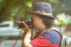 Les belles femmes asiatiques avec le sac à dos visent l'appareil-photo dans la jungle images stock