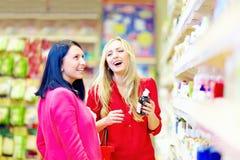 Les belles femmes choisissent le produit de soin personnel dans le supermarché Photographie stock