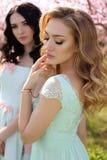 Les belles femmes dans des robes élégantes posant dans la fleur font du jardinage Photos libres de droits