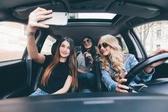 Les belles filles élégantes font le selfie, regardant l'appareil-photo ayant l'amusement tout en se reposant dans la voiture Photos stock