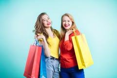 Les belles filles avec des paniers regardent l'appareil-photo et sourient tout en faisant l'achat photos libres de droits