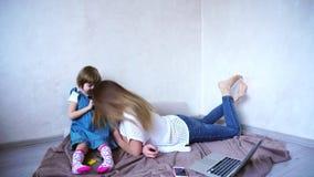 Les belles filles, la belle mère et le bébé se livrent et posent sur l'appareil-photo, jouant se reposer sur le plancher dans la  banque de vidéos