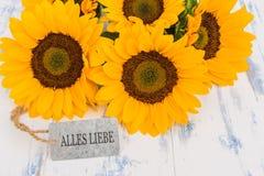 Les belles fleurs jaunes avec la carte de voeux avec le texte allemand, Alles Liebe, signifie meilleurs voeux Photographie stock libre de droits
