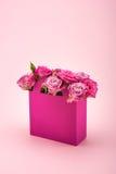 Les belles fleurs roses de floraison dans la boîte de papier décorative ont arrangé d'isolement sur le rose Images libres de droits