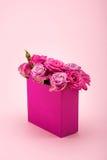 Les belles fleurs roses de floraison dans le sac de papier décoratif ont arrangé d'isolement sur le rose Photo stock