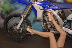 Les belles jambes minces d'une jeune fille dans des jeans court-circuite sur un bleu Photographie stock libre de droits
