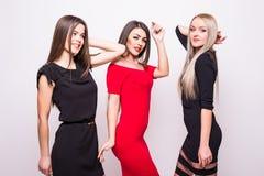 Les belles jeunes femmes dans la nuit habille la pose au-dessus du blanc Photographie stock libre de droits