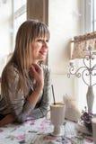 Les belles jeunes femmes s'assied à la table en café confortable et apprécie le latte parfumé Sourire et émotions positives sur s image stock