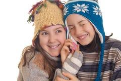 Les belles jeunes filles en hiver chaud vêtx parler d'un Mobil Photo libre de droits