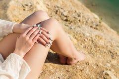 Les belles longues jambes sur le rivage du lac bleu, se trouvent les mains sur les genoux avec de longs clous acryliques Images libres de droits