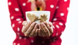 Les belles mains douces de fille tiennent les biscuits en forme de coeur de Noël doux savoureux lumineux avec une tasse de thé image stock