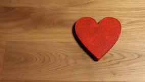 Les belles mains femelles mettant le coeur rouge forment sur la table en bois Aimez, jour du ` s de Valentine, les concepts de so banque de vidéos