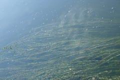 Les belles ondulations sur la rivière entrent au-dessus des pierres colorées dans le soleil d'été Photographie stock libre de droits